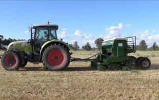 Claas tractor towing a John Shearer 3.5m Pasture Drill with Electric Drive